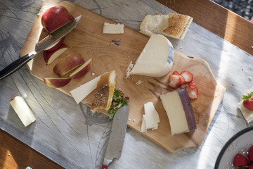 Knives and a wooden chopping board with a selection of cheeses, apples and bread.
