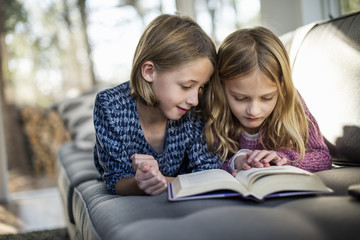 Two blond girls lying on a sofa, looking at a book.