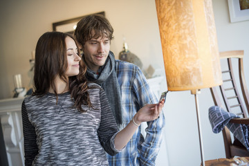 Smiling couple standing in a living room, woman holding a photograph.