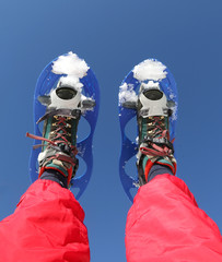 Snowshoes and Red Ski suit in the mountains