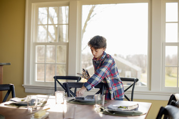 Boy setting table with cutlery and glasses
