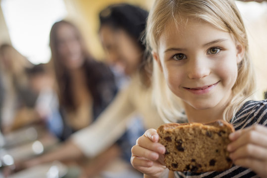 A young girl with a large cookie.