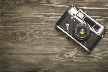 Camera. vintage old camera on brown wooden background. room for