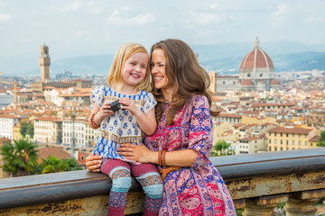 Happy mother and baby girl with photo camera in florence