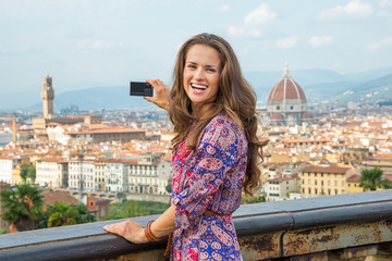 Happy young woman taking photo of panoramic view of florence