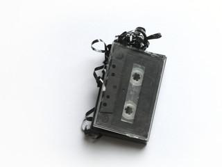 Alte Musikkassette mit Bandsalat vor weißem Hintergrund