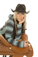cowgirl in blue and black poncho lean on saddle looking