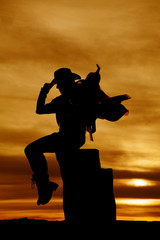 silhouette of cowgirl with saddle on her shoulder sitting lookin