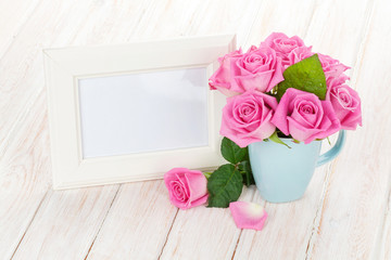 Blank photo frame and pink roses