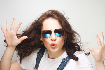 Young surprised woman wearing sunglasses.