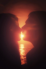 Silhouettes couple kissing at sunset