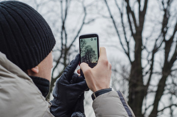 Man / tourist taking photos of a tree with mobile phone