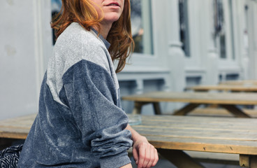 Young woman sitting on bench outside pub