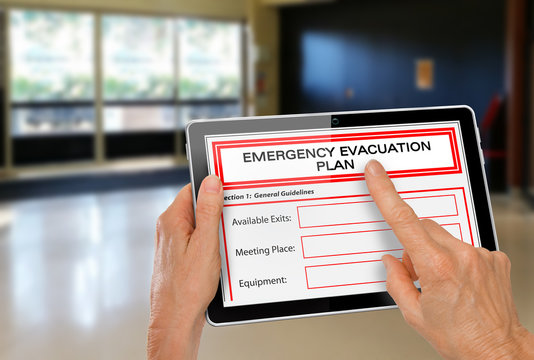 Hands with Computer Tablet and Emergency Evacuation Plan