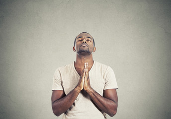 man praying hands clasped hoping for best gray background