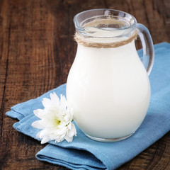 Fresh milk in a glass jug on a blue napkin