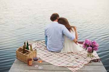 Man and woman sitting on a pier, picnic, decor, hipsters