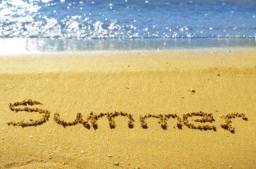 Summer written in the sand on beach with blue waves