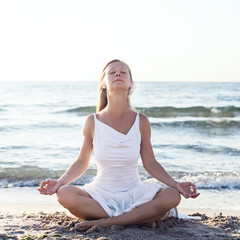 Young woman meditation on the beach