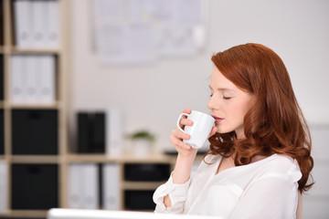 frau genießt eine tasse kaffee im büro