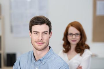 erfolgreicher junger mann mit kollegin im hintergrund