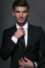 Handsome businessman adjusting his tie