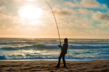 Man fishing on Beach at Sunset