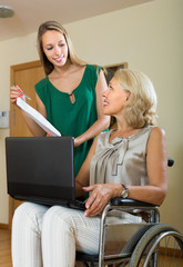 Social worker and handicapped woman with laptop