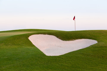 Heart shaped sand bunker in front of golf green