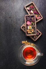Herbal tea, dried herbs and flowers on black stone background