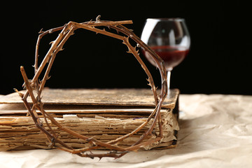 Crown of thorns and bible on black background