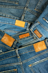 Pile of blue jeans with label