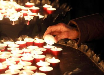 elderly woman in prayer and lit a candle
