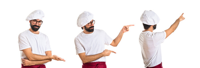 Chef pointing back over white background