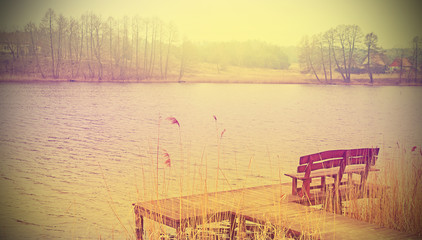 Vintage stylized photo of a wooden bench at the lake.