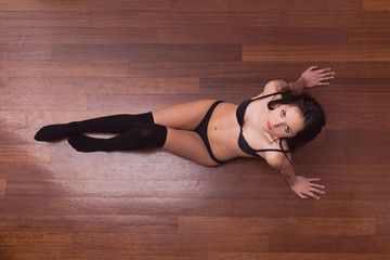 Sensual woman portrait laying on parquet floor with black underw