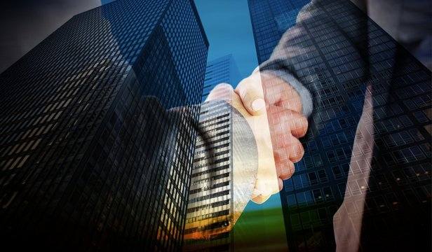Composite image of business people shaking hands close up