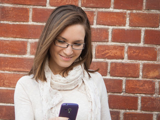 Young woman checking cell phone street
