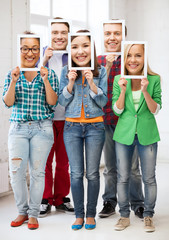 happy friends covering faces with own photos