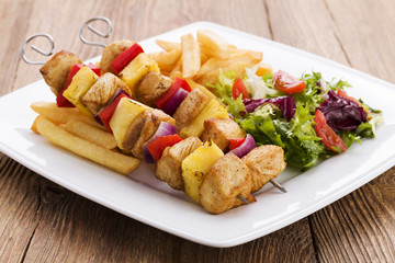 Grilled chicken skewers with pineapple, peppers and onions serve