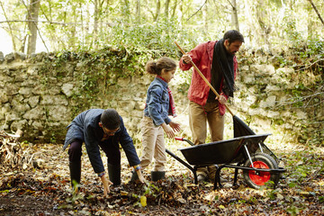 Family raking and scooping up leaves in autumn