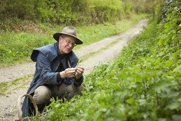 A man in a long coat and boots foraging for edible and tasty plants in the hedgerow.