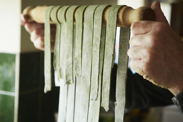 A man making fresh pasta with nettles and foraged plants.