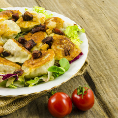 Fried dumplings with salad on wooden table