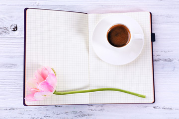 Fresh tulip, diary and cup of coffee on wooden table, top view