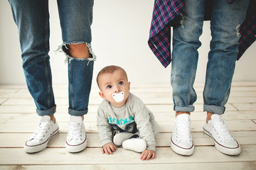 Hipster father, mother and baby boy on rustic wooden floor