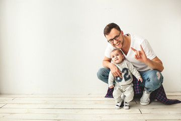 Young hipster father and baby boy on wooden floor