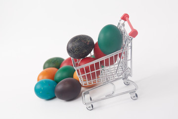 Easter colorful painted eggs in the shopping cart and near the t