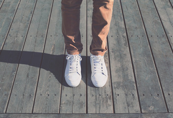 Fashion hipster cool man with white sneakers, soft vintage toned