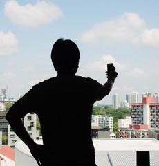 silhouette of a man akimbo position and one hand holding phone w
